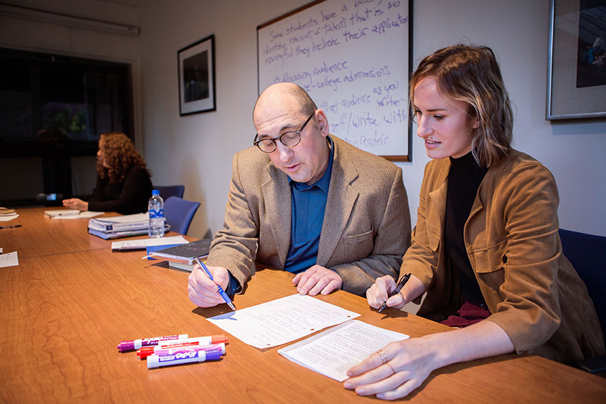 David Wolf helping student with her writing